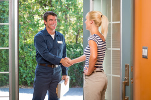 A technician greeting a woman at the front door.